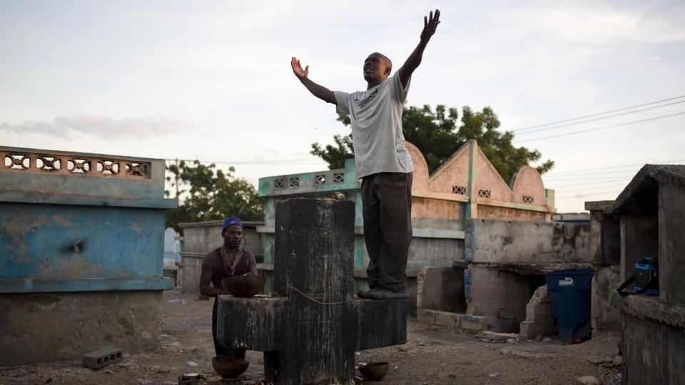 A man invokes a Gede spirit, while standing on a tomb to Baron Samdi at the Cite Soleil cemetery, in Port-au-Prince. Baron Samdi is believed to greet the recently deceased by digging up their graves and ushering their spirits into the underworld. (Dieu Nalio Chery / AP)