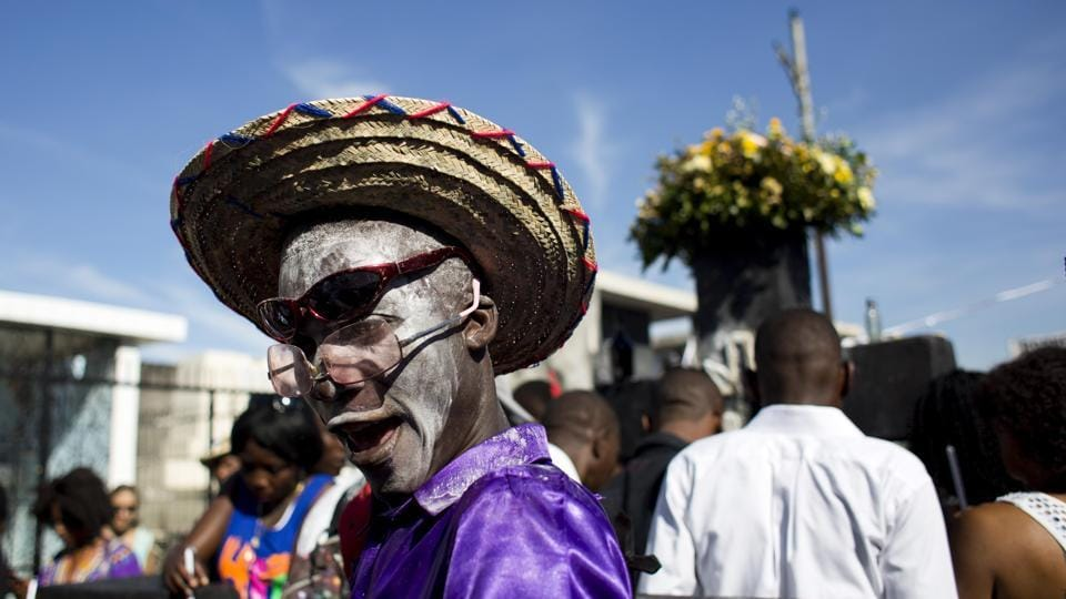 A man with his face caked in talcum powder to resemble a skull invokes a Gede spirit through chants. During celebrations revellers also honour their ancestors through song and dance, visiting their graves and presenting food from their own tables.  (Dieu Nalio Chery / AP)