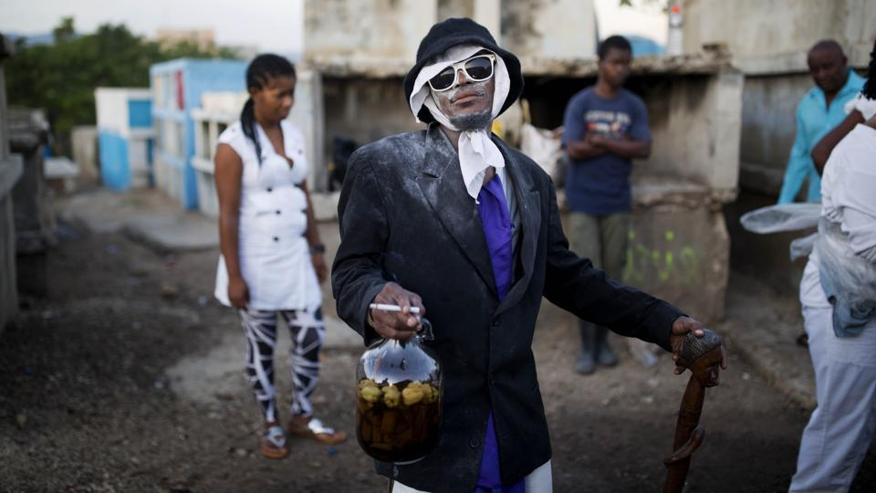 A man dressed in a black coat and glasses, holding a bottle of rum and a cigarette similar to Baron Samdi takes part in Haiti's annual Fete Gede at the National Cemetery in Port-au-Prince. Revellers streamed into cemeteries across the country in a two-day celebration to honour Baron Samdi, the guardian of the dead, ruler of graveyards and the leader of Haitian Voodoo's Gede spirits. (Dieu Nalio Chery / AP)