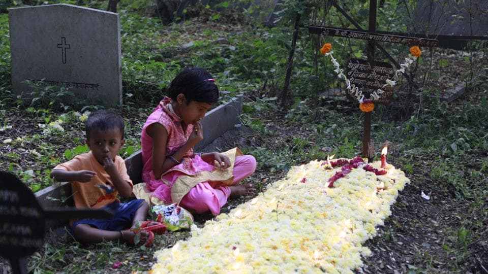 Children pay respects to the departed at the St. Sepulchre cemetery on Thursday, as Christians in the city marked November 2 as All Souls Day. (RAHUL RAUT/HT PHOTO)