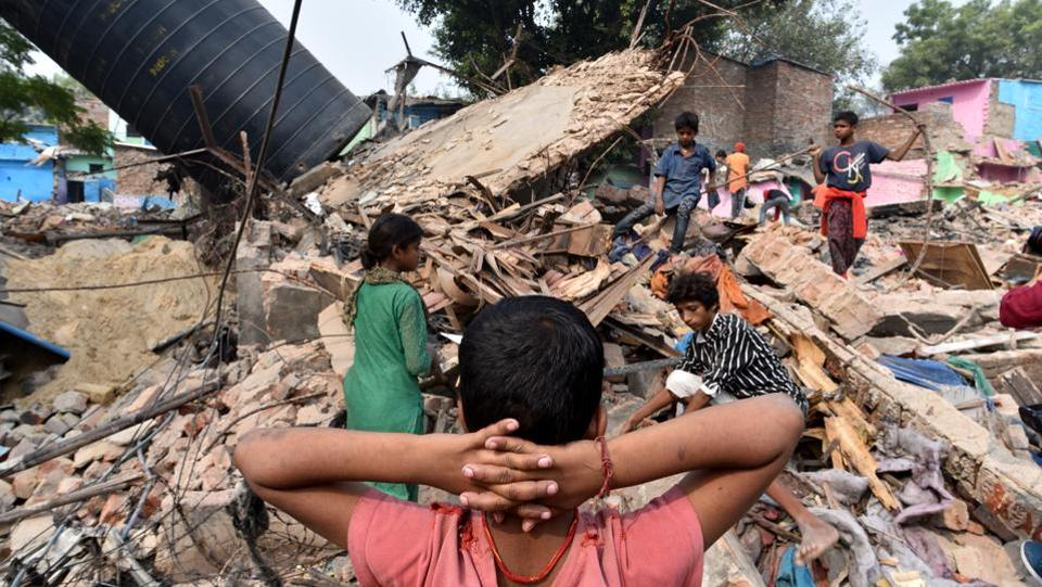 Residents look on at what's left of their homes after the Delhi Development Authority carried out a demolition drive at Katputli Colony in Shadipur, New Delhi. (Arun Sharma / HT PHOTO)