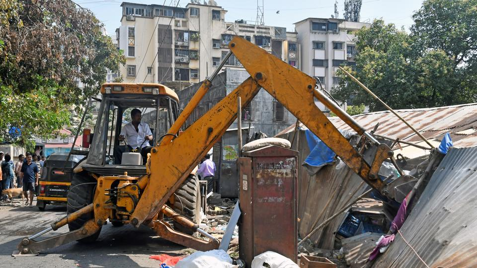A BMC worker demolishes a part of a property at Pali Naka in Mumbai on Friday.