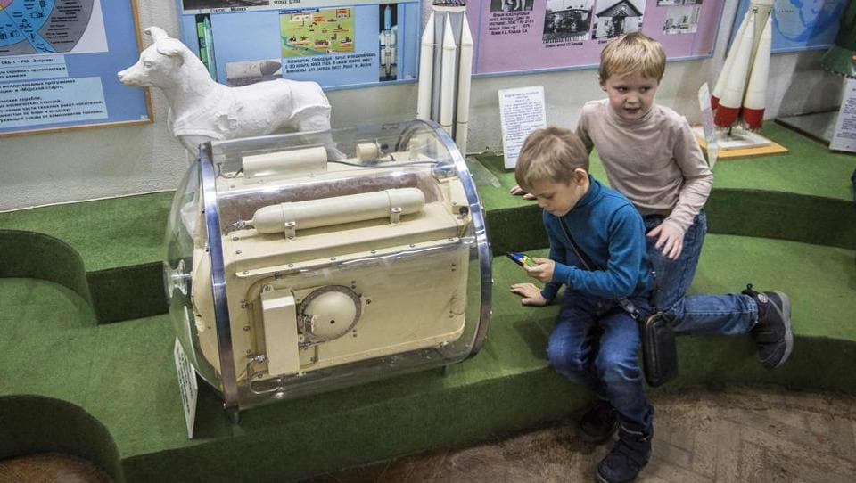 Boys play next to the space container used for Laika's trainings ahead of orbit, at the Central House of Aviation and Cosmonautics in Moscow. The official version was that she died after eating poison administered in her food to avoid a painful death on re-entry into the Earth's atmosphere. The satellite carrying her remains burnt up in the atmosphere five months later on April 14, 1958 above the Antilles islands. (Mladen Antonov / AFP)