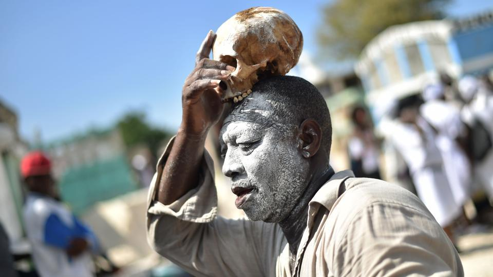 A voodoo devotee with a skull on top of his head is seen during Day of the Dead in the Cementery of Cite Soleil, in Port-au-Prince.  Fete Gede is in many ways the Haitian alternative to the Mexican  Day of the Dead, Mardi Gras and Halloween.  (Hector Retamal / AFP)