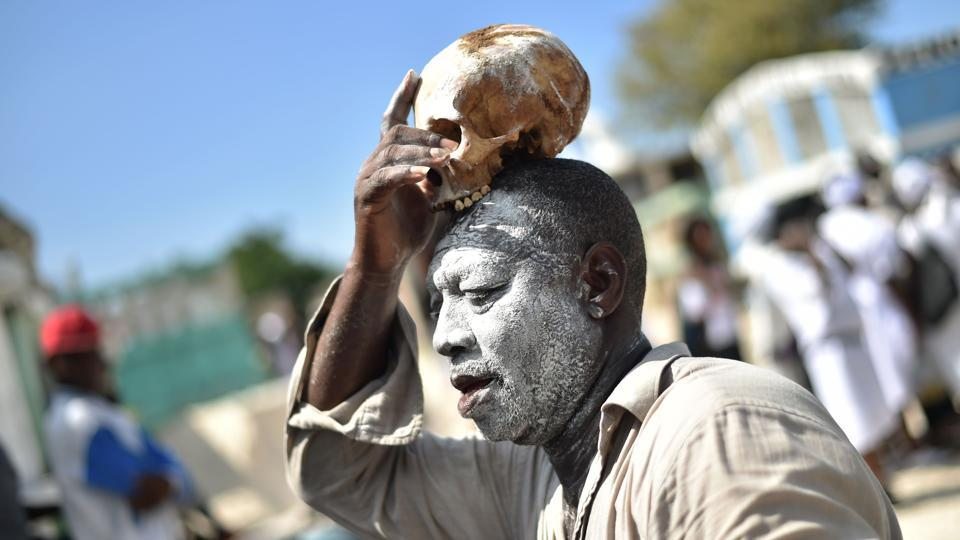 A voodoo devotee with a skull on top of his head is seen during Day of the Dead in the Cementery of Cite Soleil, in Port-au-Prince. Haitians loaded with rum, cigarettes and caked in ghostly layers of talcum took to cemeteries in the two-day Fete Gede celebration honouring dead ancestors and the master of all voodoo spirits, Baron Samdi. (Hector Retamal / AFP)