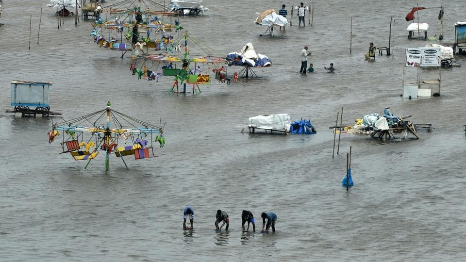 People walk through a flooded area of Marina Beach after heavy rains in Chennai on November 3, 2017.