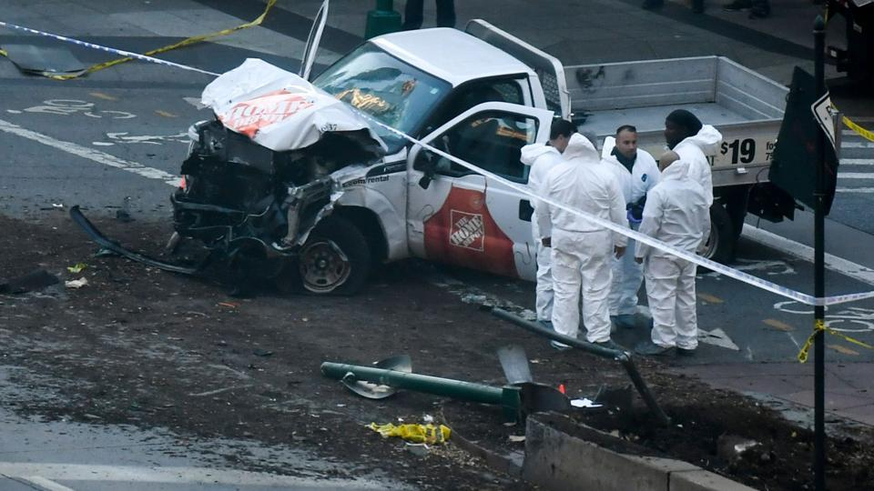 Investigators inspect a pickup truck which plowed into a pedestrian and bike path in Lower Manhattan killing eight people. The driver was shot in the abdomen by police after bailing out with what turned out to be paintball and pellet guns, shouting what witnesses said was 'Allahu Akbar'.  (Don Emmert / AFP)