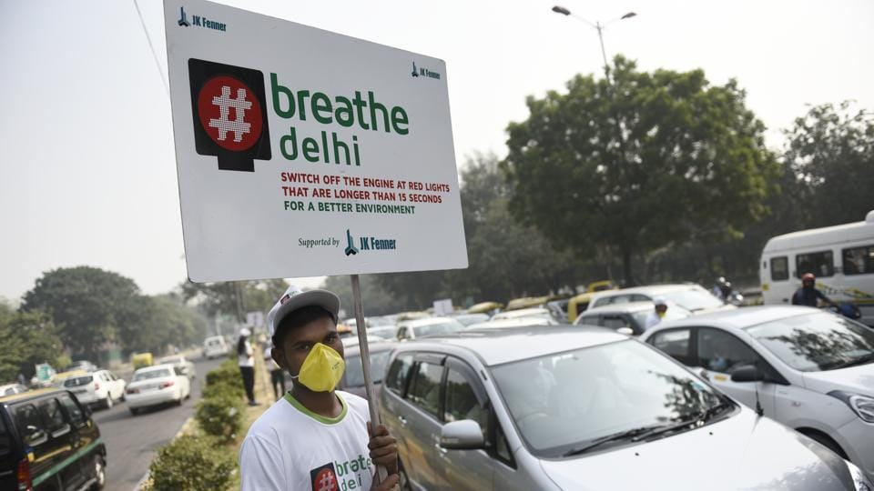 A boy wears a mask and holds a placard to address the alarming air pollution levels in the national capital.