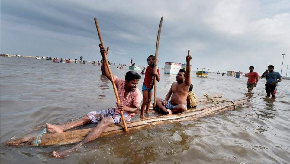 People use wooden planks as a raft to wade through floodwaters near the Marina beach shore following heavy rain in Chennai on Friday. The Tamil Nadu capital saw traffic snarls, water logging and flooding in low-lying areas as heavy showers continues to lash various parts of the city and coastal areas of the southern state. (PTI)