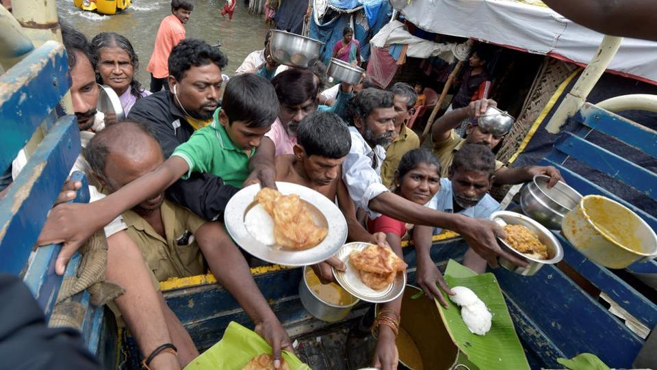 Volunteers distributed food packets and water in affected areas of Nanmangalam and Pallikaranai to residents as rain persisted for the fifth day in Chennai on Friday. A government statement said over 10,000 people were living in 105 state-run relief camps as rains flooded low-lying areas in Chennai and its suburbs on Thursday and Friday. (PTI)