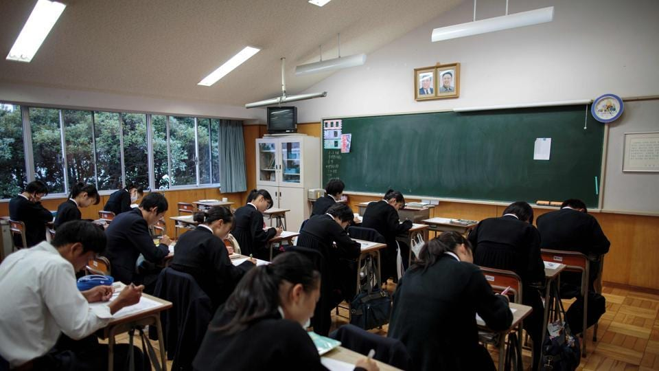 Students take an exam as portraits of late North Korean leaders Kim Il Sung and Kim Jong Il are seen in a classroom at Tokyo Korean high school in Tokyo.