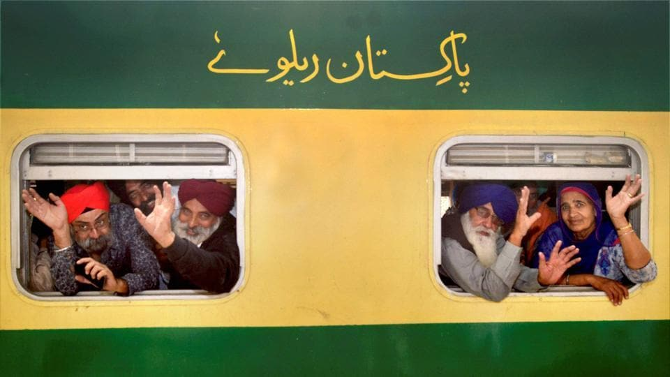 Members of a Sikh Jatha wave from train windows while departing for Pakistan to celebrate the 548th birth anniversary of Guru Nanak Dev, in Amritsar on Thursday. (PTI)