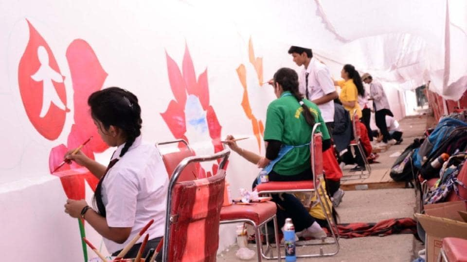 Students draw paintings on the wall of a government building in Kota.