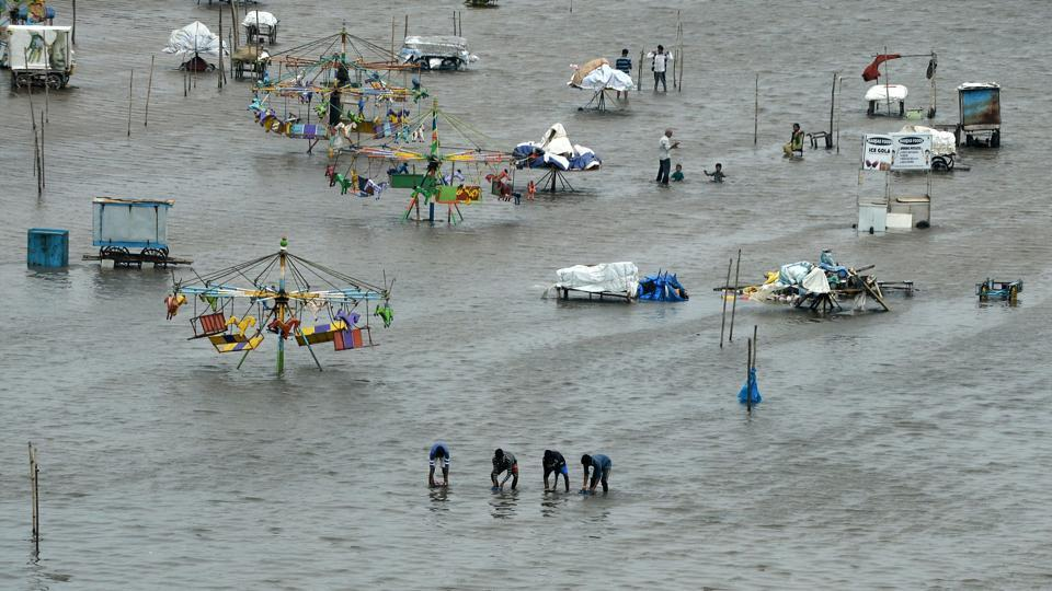 People walk through a flooded area of Marina Beach on the Bay of Bengal coast after heavy rains lashed Chennai for the eighth day.
