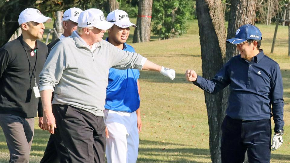 U.S. President Donald Trump gestures to Japan's Prime Minister Shinzo Abe as Japanese professional golfer Hideki Matsuyama looks on, as they play golf at the Kasumigaseki Country Club in Kawagoe, north of Tokyo, Japan, in this photo taken and released by Japan's Cabinet Public Relations Office via Kyodo November 5, 2017.