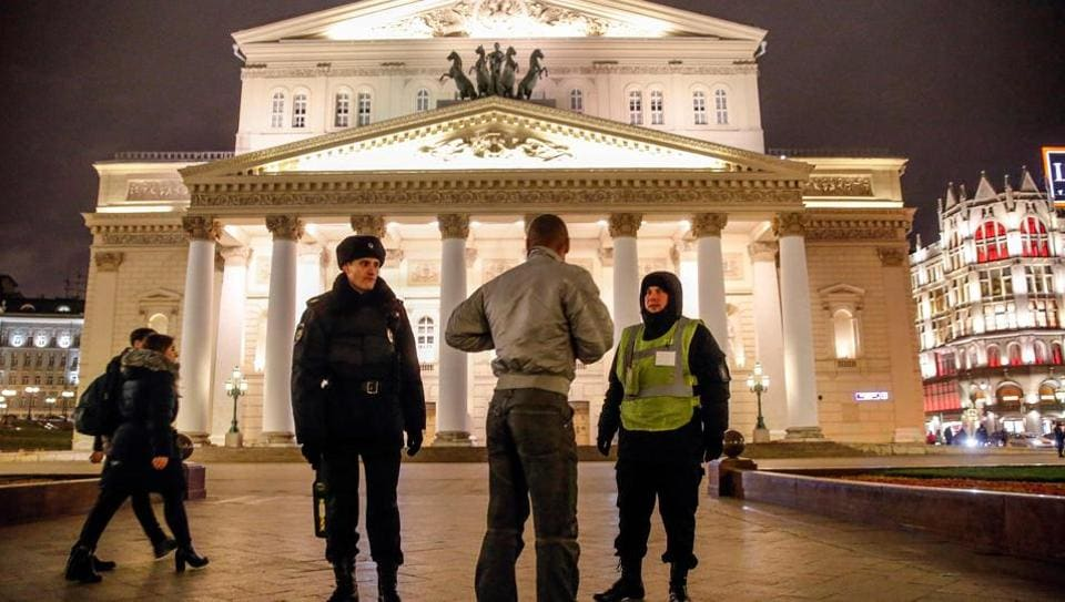 A police officer and a security staff member speak with a passerby as they stand guard in front of the Bolshoi Theatre in Moscow on November 5, 2017.