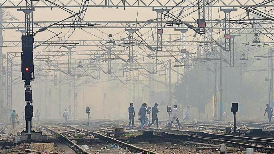 A hazy Sunday! Youngsters crossing railway tracks as smog envelops the surroundings.