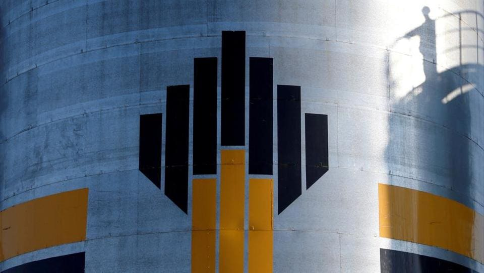 The shadow of a worker is seen next to a logo of Russia's Rosneft oil company at the central processing facility of the Rosneft-owned Priobskoye oil field outside the West Siberian city of Nefteyugansk, Russia, August 4, 2016.