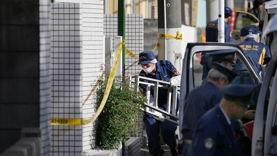 Policemen prepare for inspection in front of an apartment in Zama, Kanagawa prefecture, on November 2, where police found nine dismembered corpses.