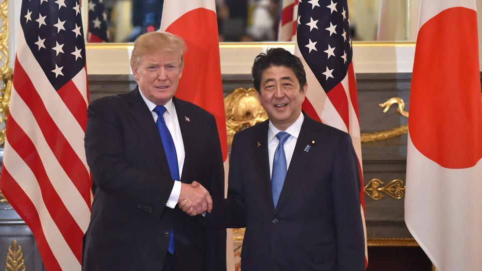 US President Donald Trump (L) shakes hands with Japanese Prime Minister Shinzo Abe (R) before a summit meeting at Akasaka Palace in Tokyo on Sunday.