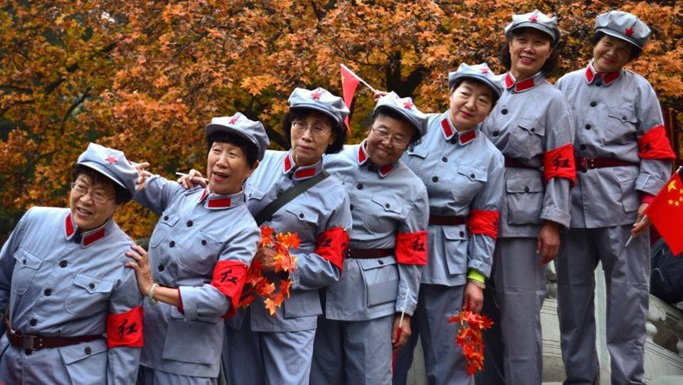 Women in replica Red Army uniforms have their picture taken with autumn leaves in the backdrop at Fragrant Hills Park in Beijing. (REUTERS)