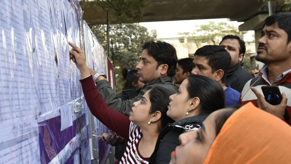 Parents look at a list of selected children for nursery class admission at Bal Bharati Public School in New Delhi.