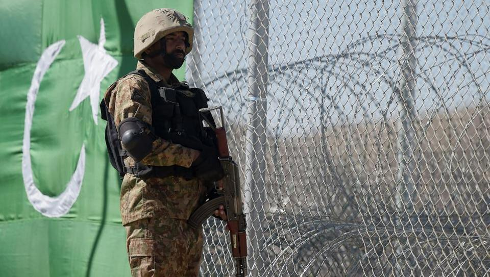 A Pakistani soldier keeps vigil next to a newly fenced border fencing along with Afghan's Paktika province border in Angoor Adda in Pakistan's South Waziristan tribal agency on October 18, 2017.