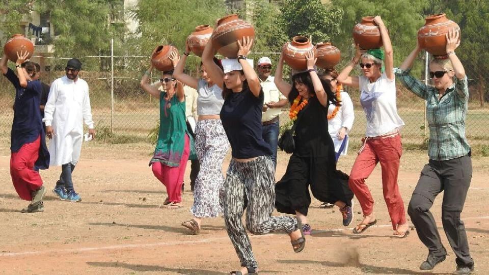 Tourists participate in Matka race at the Bundi Utsav on Monday.