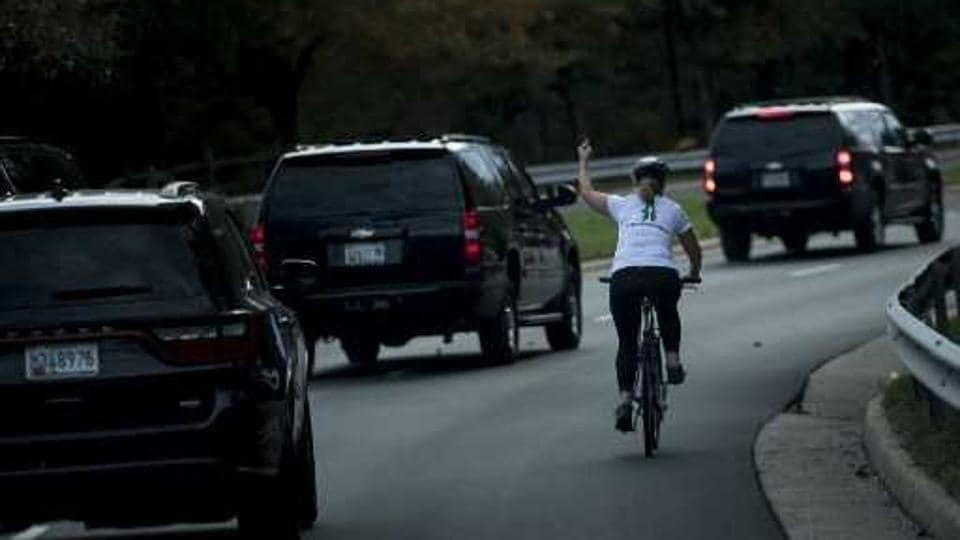 This photo taken on October 28, 2017 shows Juli Briskman on a bike gesturing with her middle finger as the motorcade of US President Donald Trump drives past, in Sterling, Virginia.