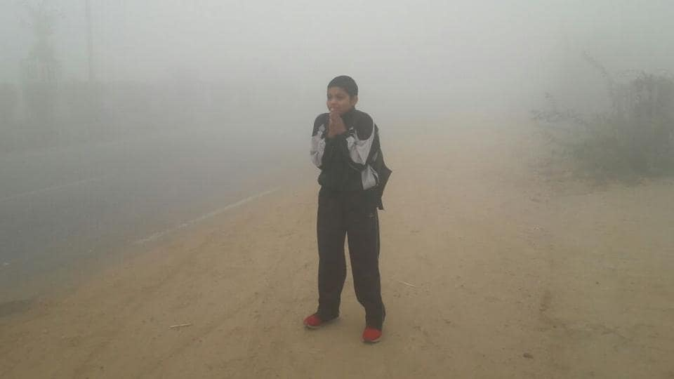 A student waiting for his schoolbus amid dense smog in Rohtak on Tuesday.  (Manoj dhaka/HT)