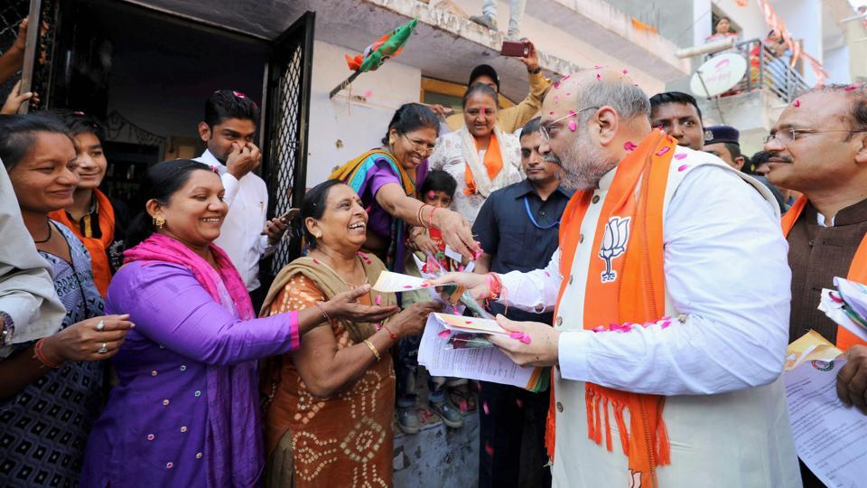 BJP president Amit Shah distributes copies of Prime Minister Narendra Modi's message during his door-to-door campaign for the assembly polls in Naranpura in Gujarat on Tuesday.