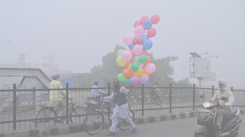 Trying to brighten things up, a vendor sells balloons during 'smoggy' weather in Amritsar on Tuesday.  (Sameer Sehgal/HT)