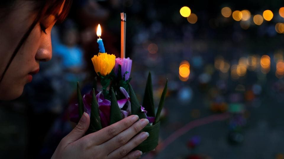 A girl prays before casting a krathong into a pond at a public park during the Loy Krathong festival. Participants in the festival pay respects to the water spirits by floating small, traditionally-hand crafted rafts carrying flowers, bamboo and candles on waterways in this  ancient ritual. (Jorge Silva / REUTERS)