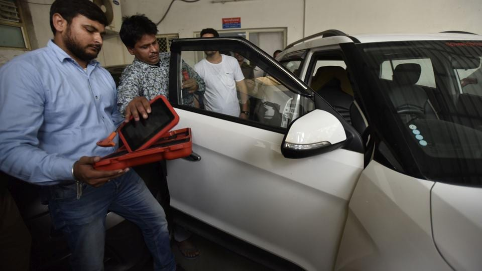 A member of the gang gives demonstration on how they used to open a car door, after arrest by Noida police on Tuesday.