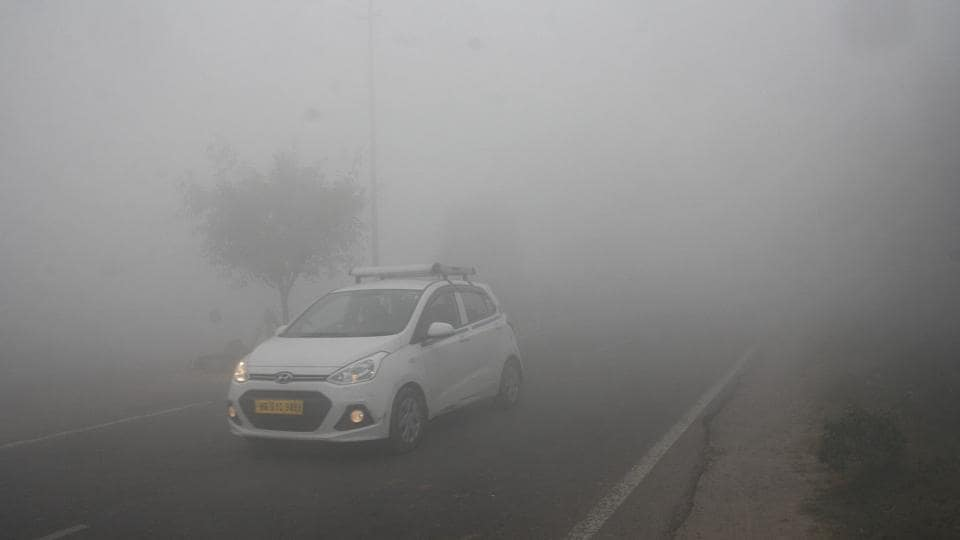 Vehicles passing through dense fog on the Rohtak-Delhi road (NH-10) in Rohtak.  (Ht Photo)