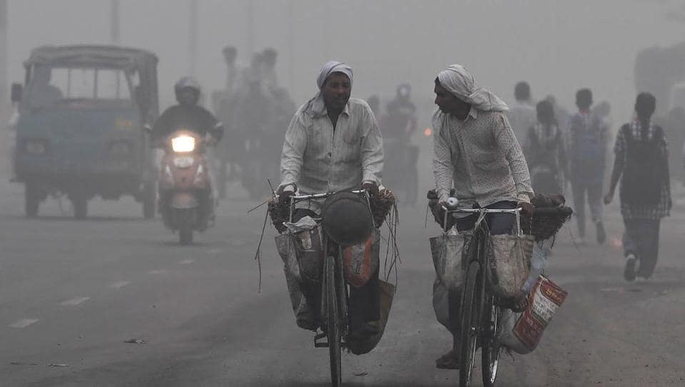 Commuters drive amid heavy smog in New Delhi on Tuesday. The city woke up to a choking blanket of smog as air quality in the world's most polluted capital city reached hazardous levels.