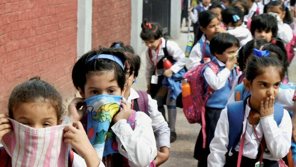 Schoolchildren cover their noses as air pollution reached severe levels in New Delhi on Tuesday.