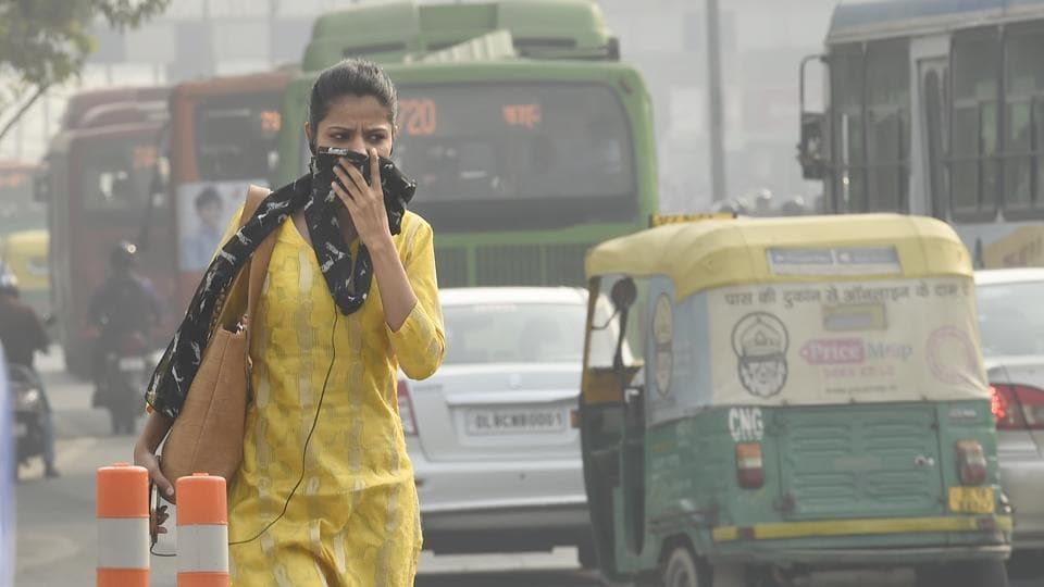 A woman covers her face with a scarf to minimise the impact of toxic air at ITO crossing in New Delhi.