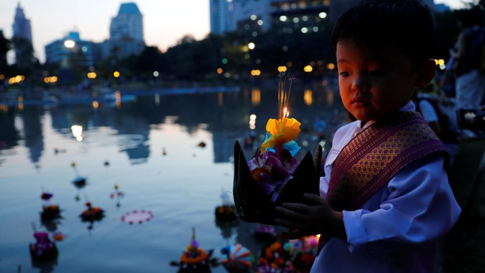 A boy dressed in traditional Thai clothes prepares to place a krathong (floating basket) into a pond at a public park during the Loy Krathong festival in Bangkok. People in Thailand celebrated the Loy Krathong or 'floating basket' festival and Yee Peng festival (festival of lights), following a year of mourning for late King Bhumibol Adulyadej that saw many celebrations muted or cancelled. (Jorge Silva / REUTERS)