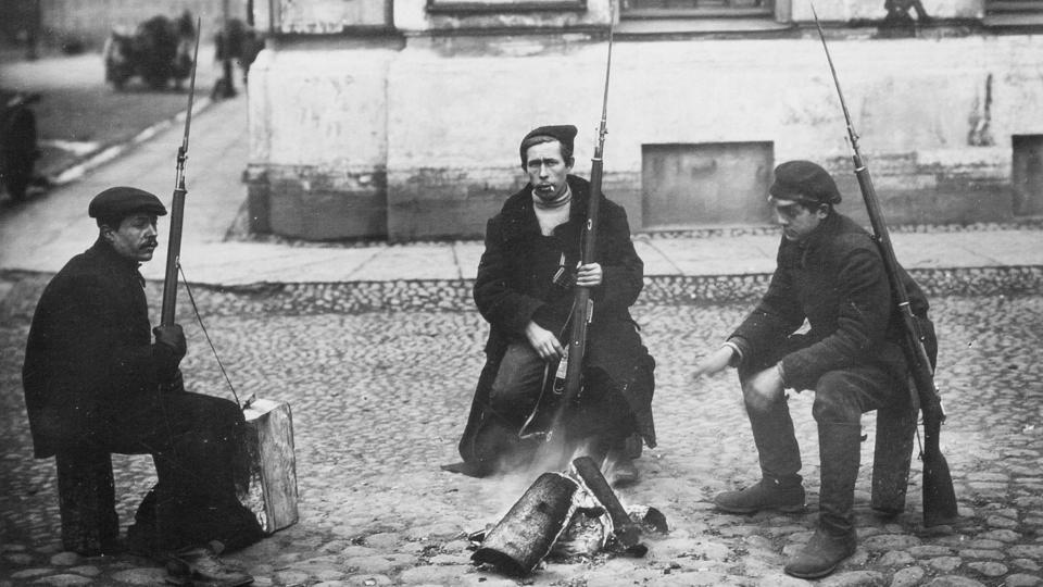 Armed revolution workers Ivanov, Yarosh and Gribovsky (L-R) warm themselves at a bonfire in St.Petersburg, Russia in October 1917. On October 25 1917 (November 07, Gregorian calendar) the Red Guard under the authority of the Bolshevik Central Committee launched an armed uprising in Petrograd to seize government facilities, communication and vantage locations, to little opposition.  (Russian State Archive of Social and Political History via AP)