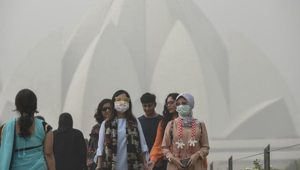 Foreign tourists wear masks as they visit the Lotus Temple on a smoggy morning in New Delhi on Tuesday.
