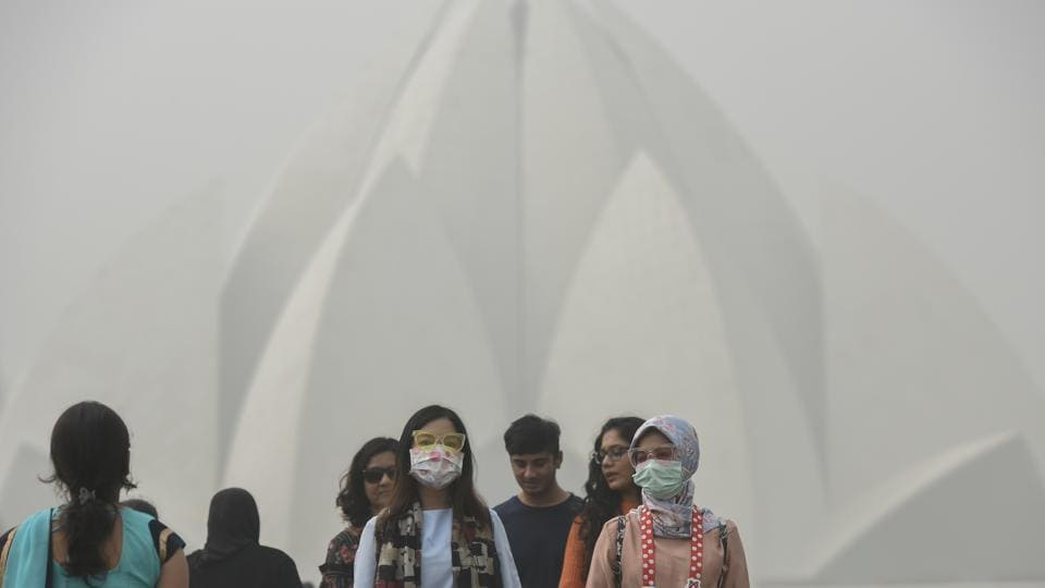 Tourists wearmasks as they visit Lotus Temple amid heavy smog in Delhi on November 7. Delhi woke up to a choking blanket of smog on November 7 as air quality in the city reached hazardous levels.