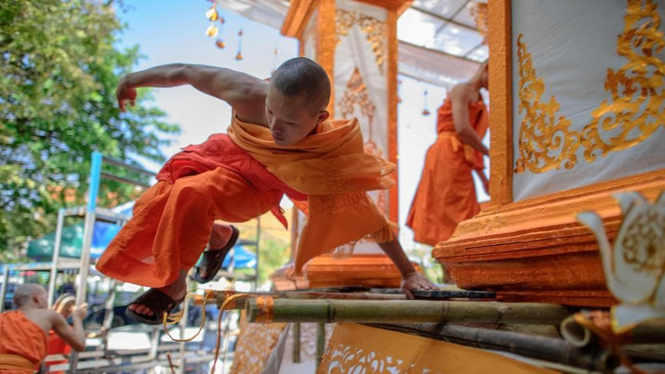 A Buddhist monk jumps off a float at the Phra Singh Buddhist temple in Chiang Mai during preparations for a float parade. (Roberto Schmidt / AFP)