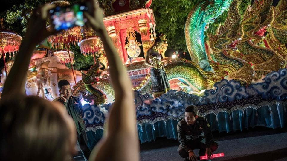 Policemen guard a parade float as a spectator uses her mobile to take a photograph of the scene in a street of downtown Chiang Mai. Thousands of people that include tourists and locals alike line the streets to watch the display of elaborate floats. (Roberto Schmidt / AFP)