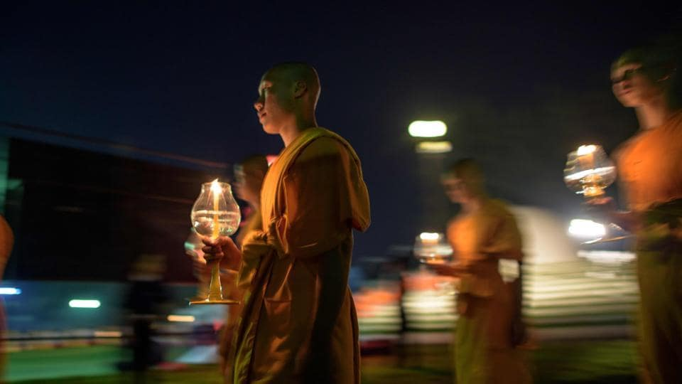 Buddhist monks carry lit candles as they participate in a procession around a shrine of Buddha during the celebration of the Yee Peng festival, also known as the festival of lights. The main part of this celebration here was the collective releasing of lit lanterns into the sky later in the evening. (Roberto Schmidt / AFP)
