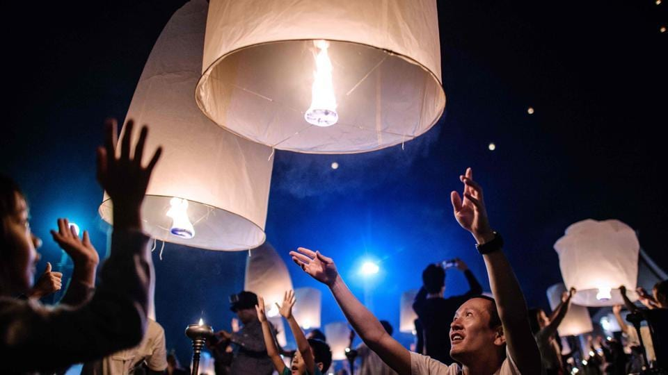 People releases lanterns into the air as they celebrate the Yee Peng festival. The festivals are thought to carry away bad luck and usher in good fortune. (Roberto Schmidt / AFP)
