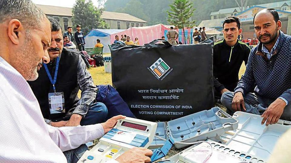 An employee on election duty checking electronic voting machines (EVM) before leaving for the poling station in Mandi on Tuesday.