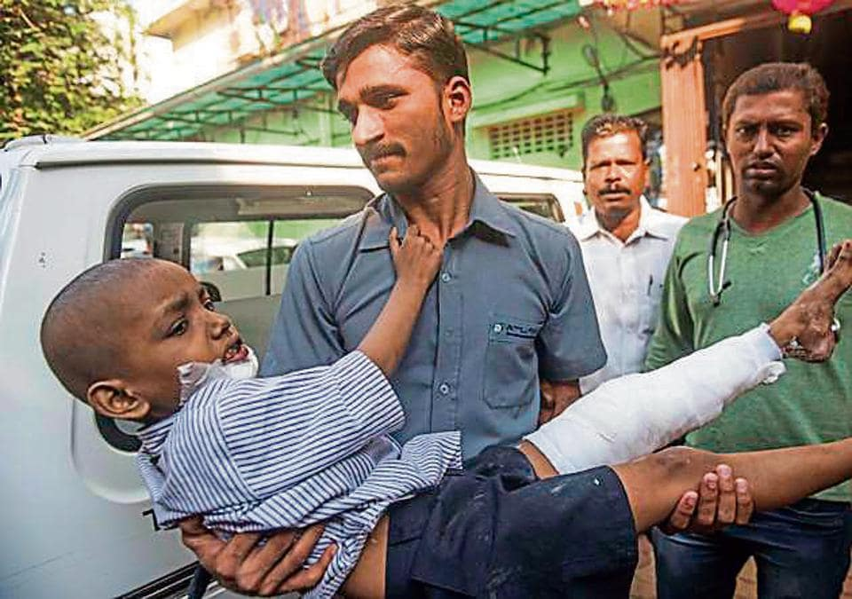 Kamal Mewati, one of the injured siblings, being carried to an ambulance in Mumbai.