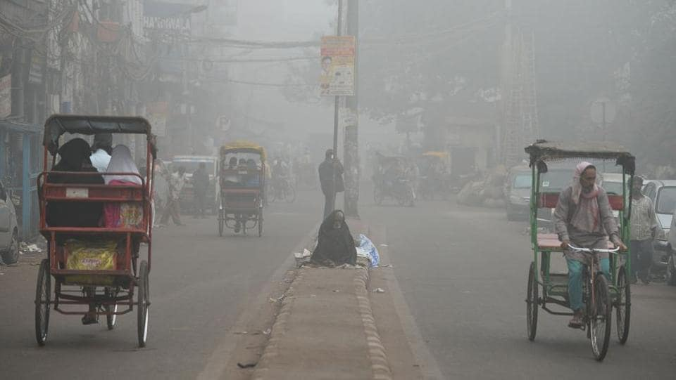 A homeless person sits on a road median amid heavy smog in New Delhi.