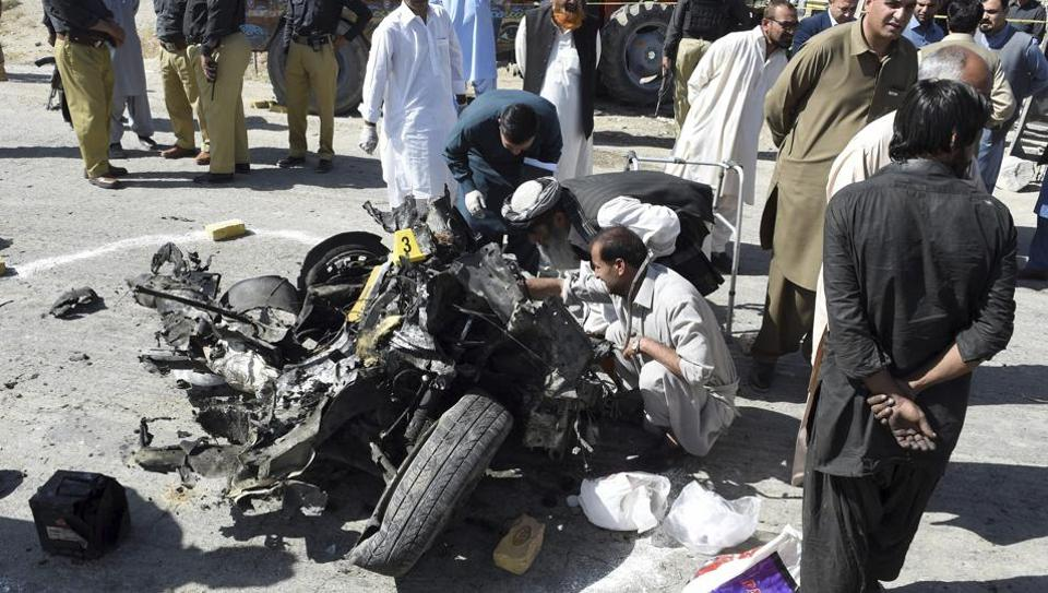 Pakistani officials examine a wreckage of a vehicle following a car bomb attack on a police truck killing many people in Quetta, Pakistan on October 18.